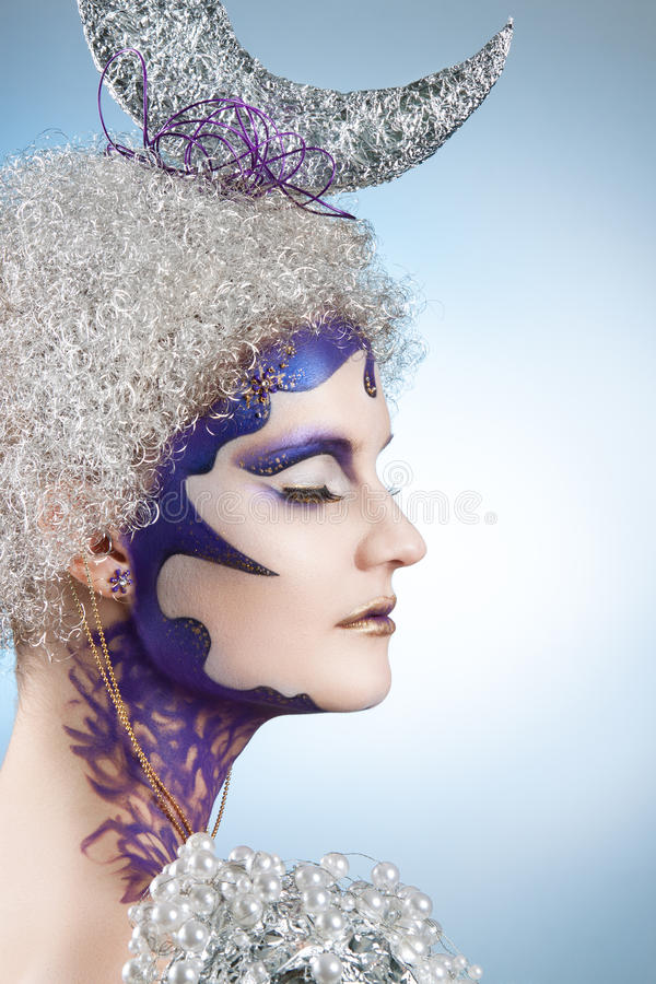 Winter portrait of a girl with creative make-up on a light background. Purple - Gold Makeup. Lunar silver in the hair of curls. Woman with eyes closed royalty free stock images