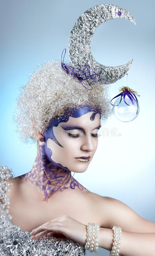 Winter portrait of a girl with creative make-up on a light background. Purple - Gold Makeup. Lunar silver in the hair of curls. Woman with eyes closed stock photography