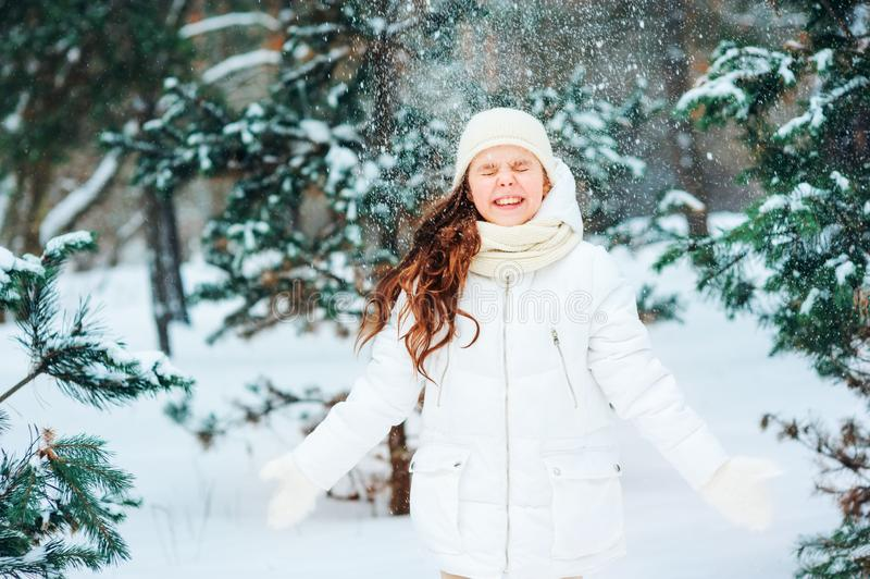 Winter portrait of happy child girl in white coat, hat and mittens playing outdoor in snowy winter forest stock photo