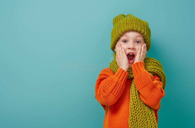 Winter portrait of happy child. Wearing knitted hat, snood and sweater. Girl having fun, playing and laughing on teal background. Fashion concept stock images
