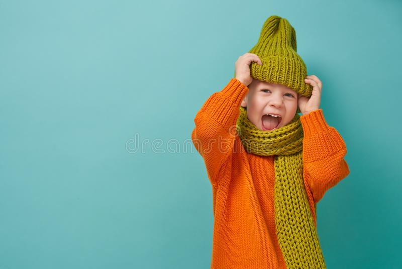 Winter portrait of happy child. Wearing knitted hat, snood and sweater. Girl having fun, playing and laughing on teal background. Fashion concept royalty free stock image