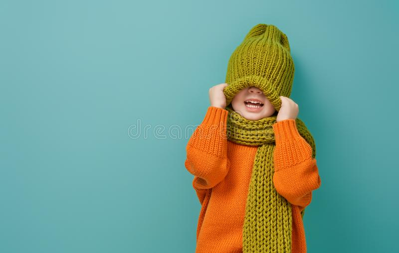Winter portrait of happy child. Wearing knitted hat, snood and sweater. Girl having fun, playing and laughing on teal background. Fashion concept royalty free stock photography
