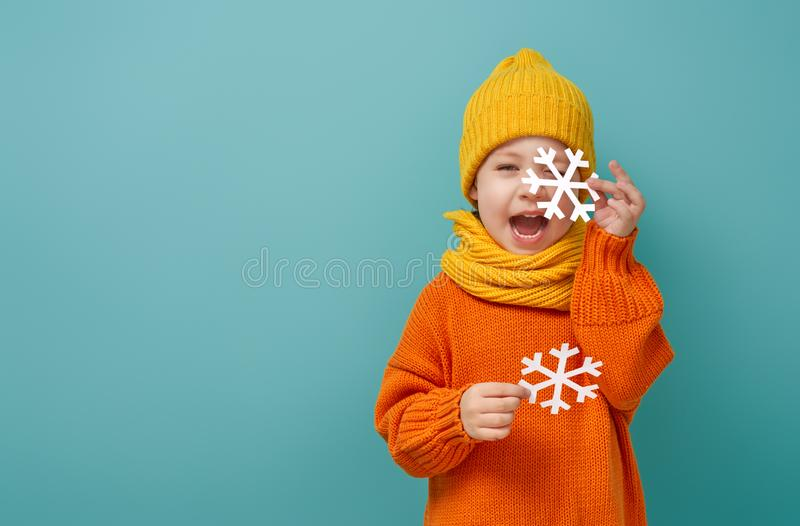 Winter portrait of happy child. Wearing knitted hat, snood and sweater. Girl having fun, playing and laughing on teal background. Fashion concept stock photos