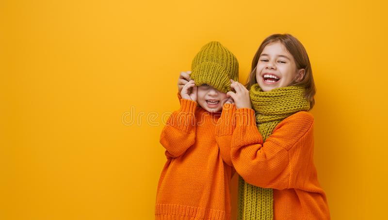 Winter portrait of happy children. Wearing knitted hat, snood and sweaters. Girls having fun, playing and laughing on yellow background. Fashion concept royalty free stock photography