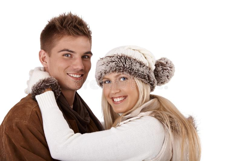 Winter portrait of happy couple. Smiling in embrace, looking at camera, wearing hat and gloves and coat stock images