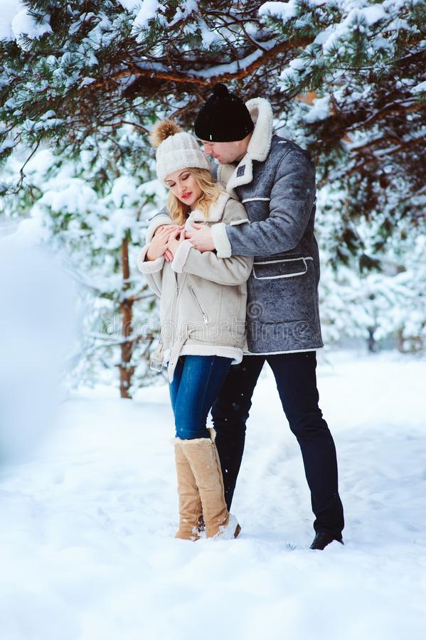 winter portrait of happy couple having fun in snowy forest royalty free stock photo