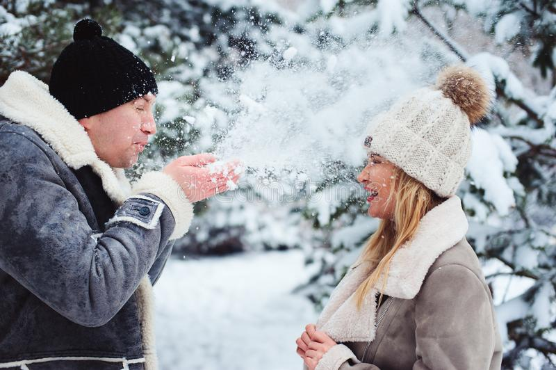 Winter portrait of happy couple playing, blowing snow and spending good day outdoor in snowy forest. Seasonal activities on Holidays royalty free stock photos