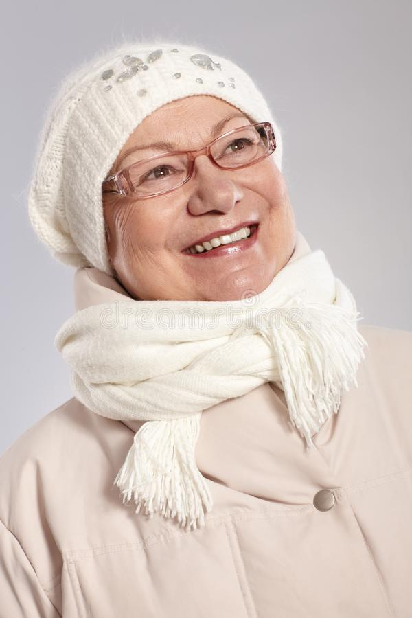 Winter portrait of happy elderly lady. In warm clothes, looking away royalty free stock photos