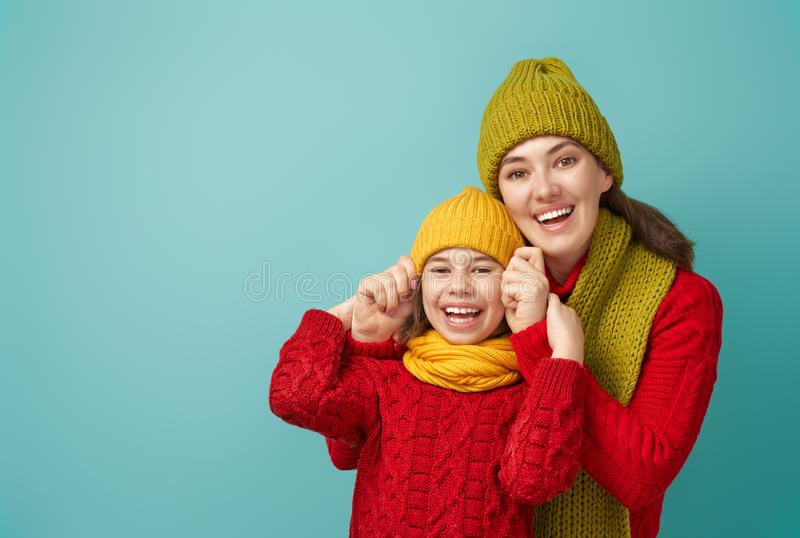 Winter portrait of happy family. Winter portrait of happy loving family wearing knitted hats, snoods and sweaters. Mother and child girl having fun, playing and royalty free stock photo