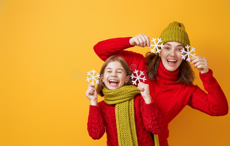 Winter portrait of happy family. Winter portrait of happy loving family wearing knitted hats, snoods and sweaters. Mother and child girl having fun, playing and royalty free stock photography