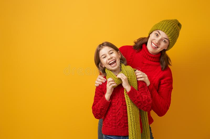 Winter portrait of happy family. Winter portrait of happy loving family wearing knitted hats, snoods and sweaters. Mother and child girl having fun, playing and royalty free stock image