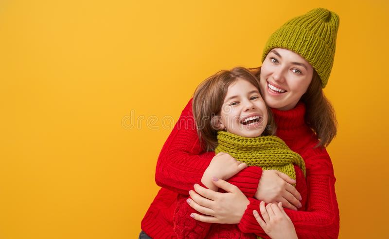 Winter portrait of happy family. Winter portrait of happy loving family wearing knitted hats, snoods and sweaters. Mother and child girl having fun, playing and stock photos