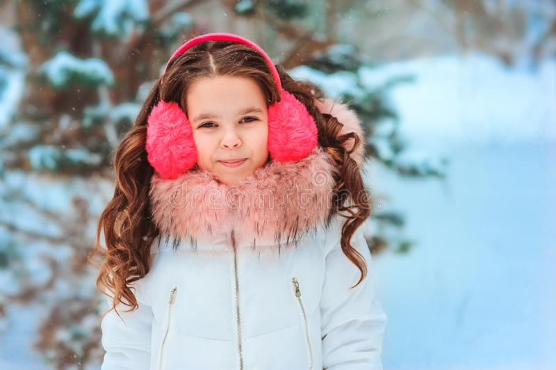 Winter portrait of happy kid girl in pink earmuffs walking outdoor in snowy winter forest. Happy childhood and active winter holidays concept stock photo