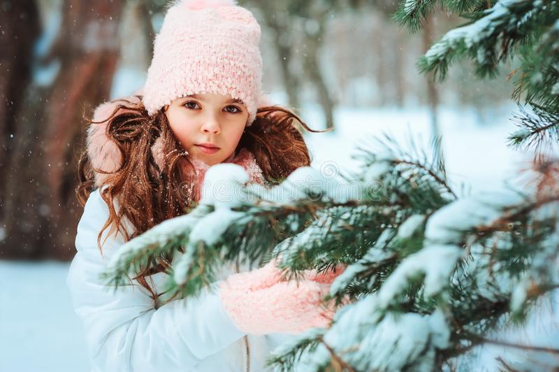 Winter portrait of happy kid girl in white coat and pink hat and mittens playing outdoor in snowy winter forest with snow covered. Fir branch. Traveling stock images