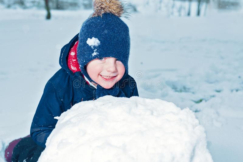 Winter portrait of a happy little boy. kid laughs and smiles. child makes a snowman. emotion happiness royalty free stock photo