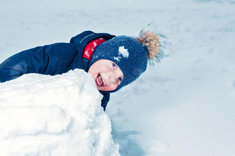 Winter portrait of a happy little boy. kid laughs and smiles. child makes a snowman. emotion happiness royalty free stock images