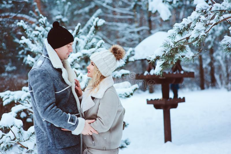 Winter portrait of happy romantic couple embracing and looking to each other outdoor in snowy day. Spending Christmas vacations in forest or park royalty free stock image