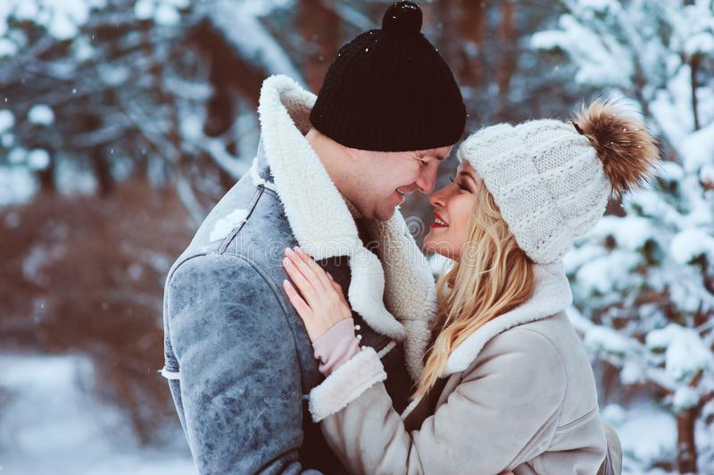 Winter portrait of happy romantic couple embracing and looking to each other outdoor in snowy day. Spending Christmas vacations in forest or park royalty free stock images