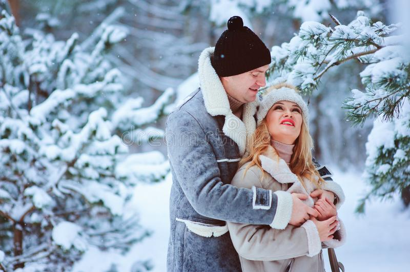 winter portrait of happy romantic couple enjoying their walk in snowy forest or park royalty free stock photos
