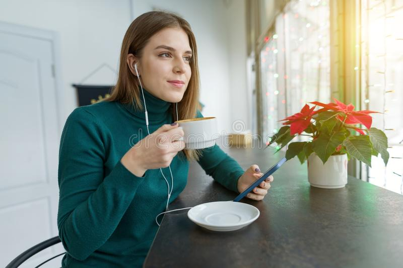 Winter portrait of happy smiling girl in headphones with mobile phone and drinking coffee in coffee shop. Young woman looking out royalty free stock image