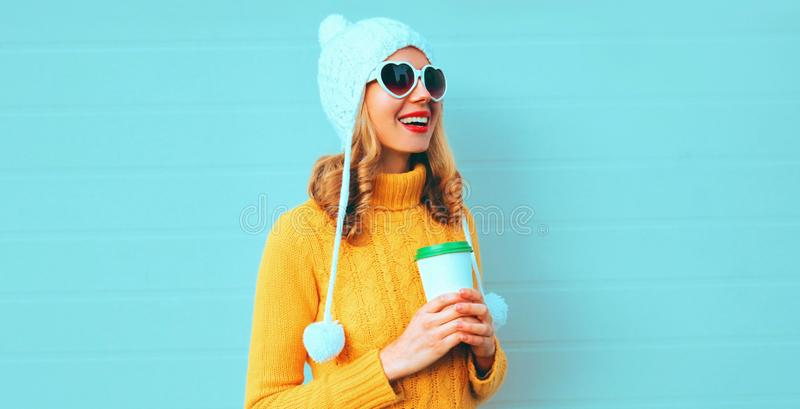 Winter portrait happy smiling young woman with coffee cup looking away wearing yellow knitted sweater, white hat with pom pom stock photography
