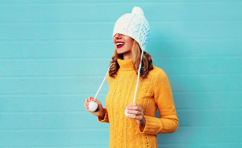 Winter portrait happy smiling young woman having fun pulls a hat over her eyes wearing yellow knitted sweater and white hat royalty free stock photography