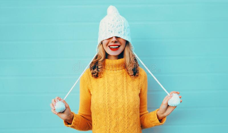 Winter portrait happy smiling young woman having fun pulls a hat over her eyes wearing yellow knitted sweater royalty free stock photo