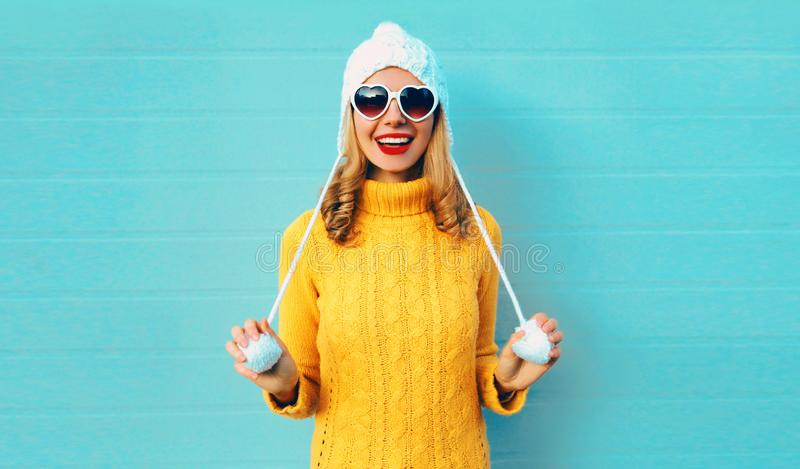 Winter portrait happy smiling young woman having fun wearing yellow knitted sweater and white hat with pom pom royalty free stock photography