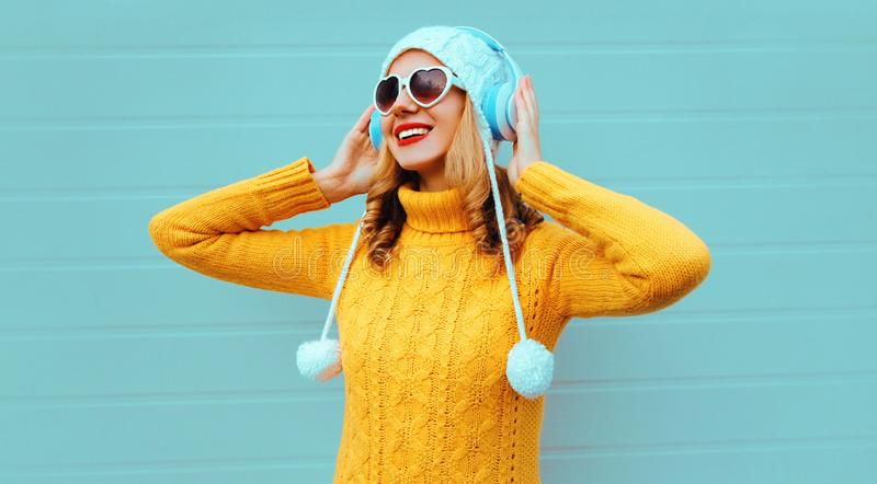 Winter portrait happy smiling young woman in wireless headphones listening to music wearing yellow knitted sweater and white hat royalty free stock photography