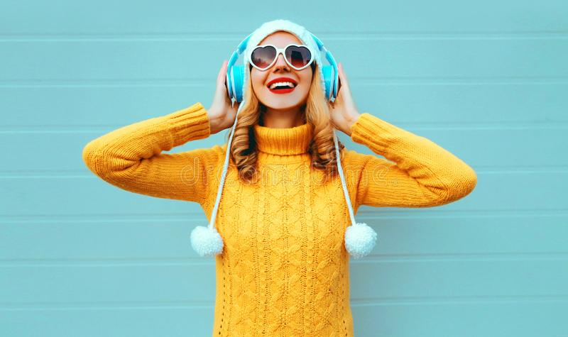 Winter portrait happy smiling young woman in wireless headphones listening to music wearing yellow knitted sweater and white hat stock photos