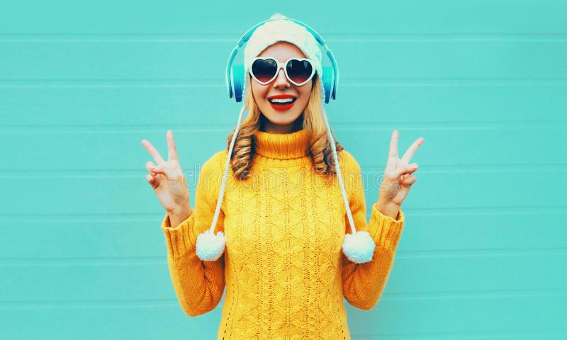 Winter portrait happy smiling young woman in wireless headphones listening to music wearing yellow knitted sweater and white hat royalty free stock photo