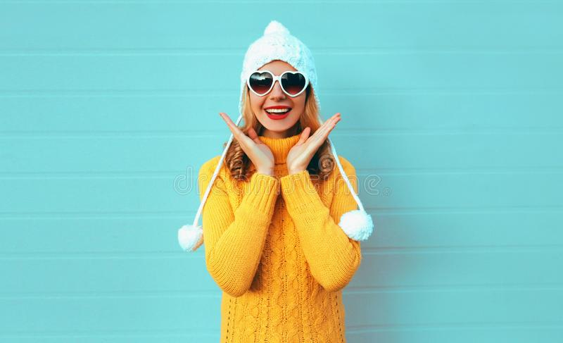 Winter portrait happy surprised young woman wearing yellow knitted sweater and white hat with pom pom, heart shaped sunglasses royalty free stock photography