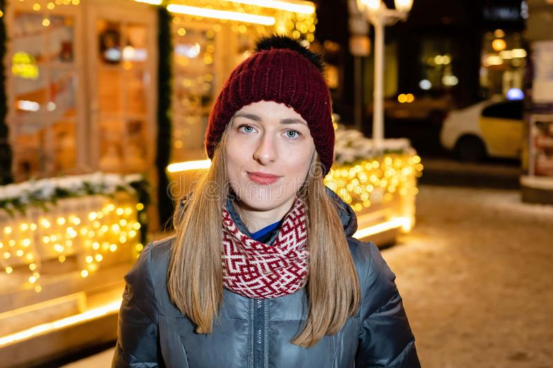 Winter portrait of happy young woman walking in snowy city decorated for Christmas and New Year holidays. stock photos