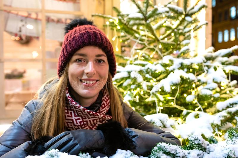 Winter portrait of happy young woman walking in snowy city decorated for Christmas and New Year holidays. royalty free stock photo