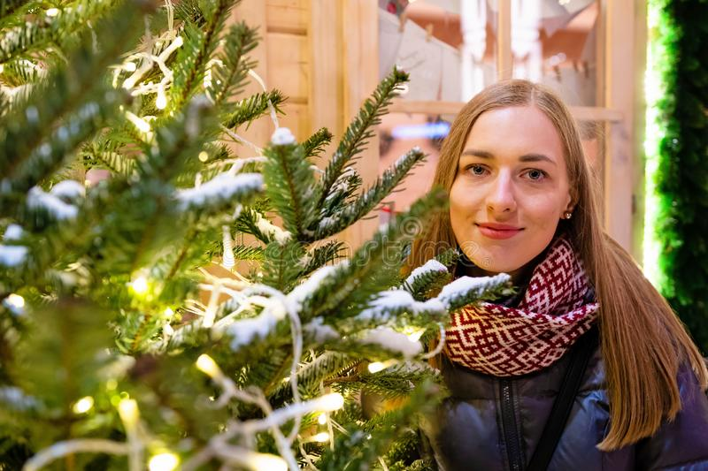 Winter portrait of happy young woman walking in snowy city decorated for Christmas and New Year holidays. stock photography