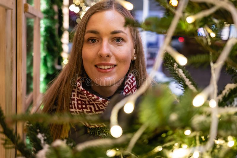 Winter portrait of happy young woman walking in snowy city decorated for Christmas and New Year holidays. stock image