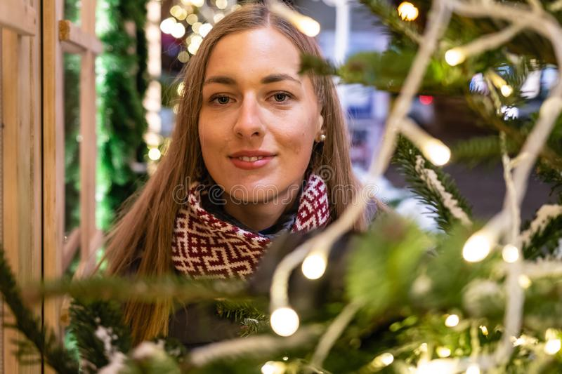 Winter portrait of happy young woman walking in snowy city decorated for Christmas and New Year holidays. royalty free stock image