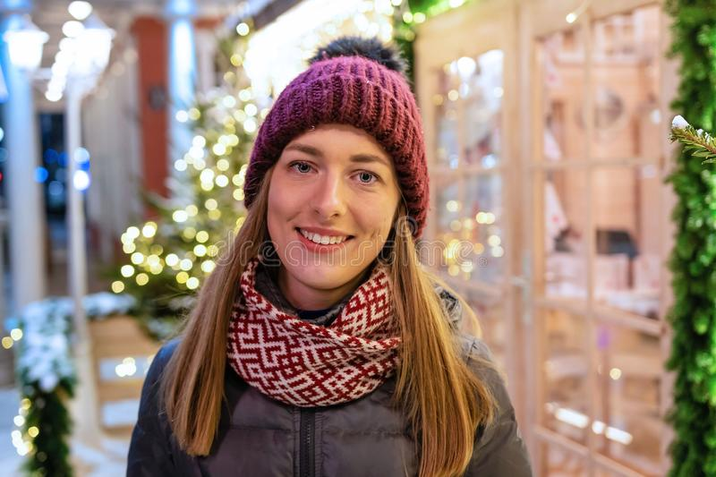 Winter portrait of happy young woman walking in snowy city decorated for Christmas and New Year holidays. royalty free stock images
