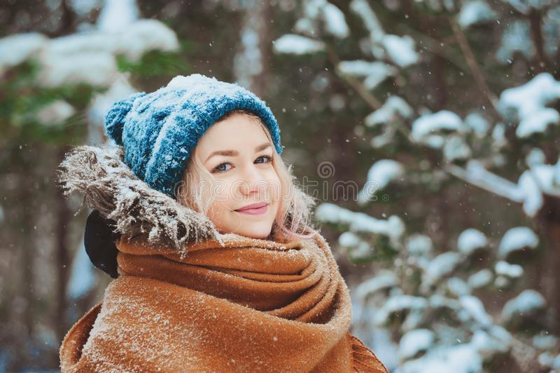 Winter portrait of happy young woman walking in snowy forest in warm outfit, knitted hat and oversize scarf. Exploring nature on winter and Christmas vacations stock image