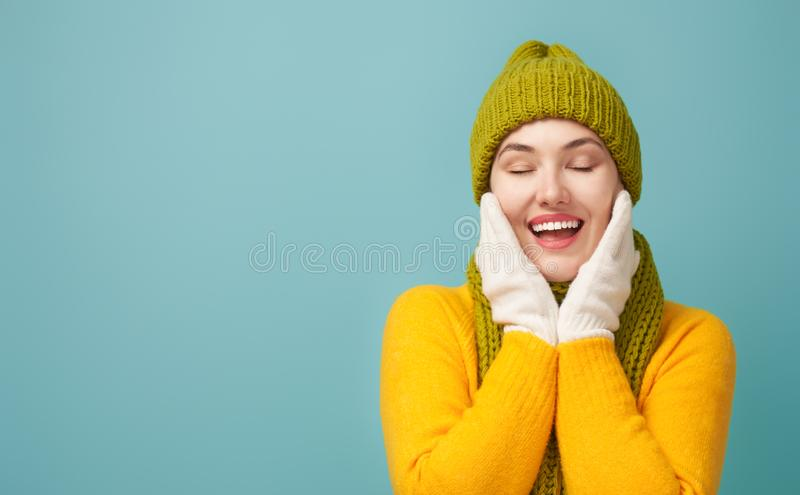 Winter portrait of happy young woman. Wearing knitted hat, scarf and sweater. Girl having fun on bright teal background. Fashion concept stock images