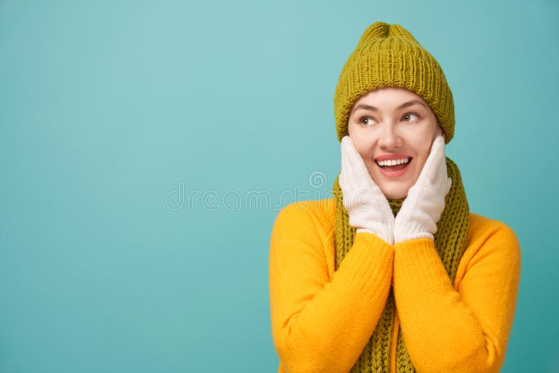 Winter portrait of happy young woman. Wearing knitted hat, scarf and sweater. Girl having fun on bright teal background. Fashion concept royalty free stock image