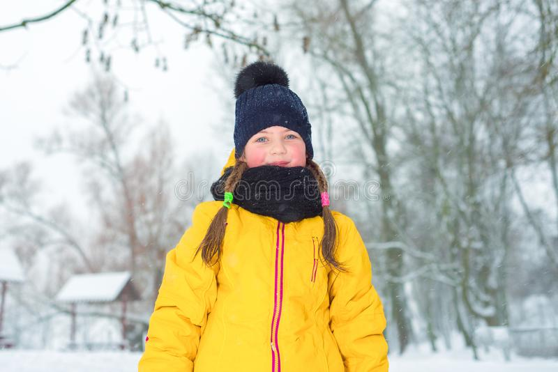 Winter portrait of little girl with pigtails in jacket and blue hat in winter royalty free stock image