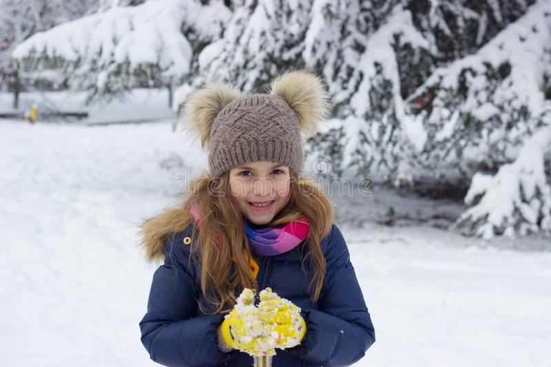 Winter portrait of a smiling beautiful little girl on the snow royalty free stock images