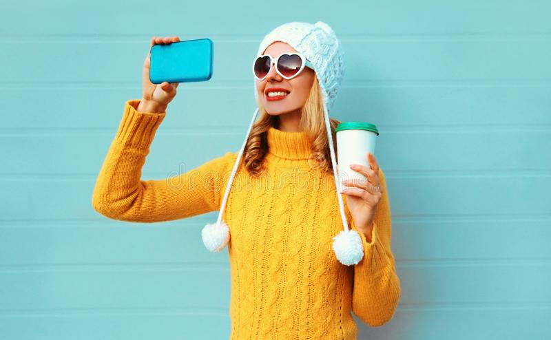 Winter portrait smiling woman taking selfie picture by phone with coffee cup wearing yellow knitted sweater, white hat stock images