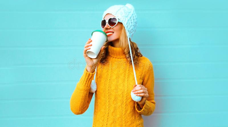 Winter portrait smiling young woman drinking coffee looking away wearing yellow knitted sweater, white hat with pom pom royalty free stock photography