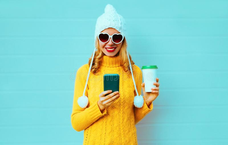 Winter portrait smiling young woman with phone and coffee cup wearing yellow knitted sweater, white hat with pom pom stock photo