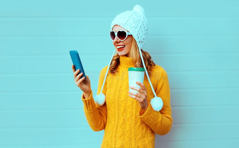 Winter portrait smiling young woman with phone and coffee cup wearing yellow knitted sweater, white hat with pom pom royalty free stock photography