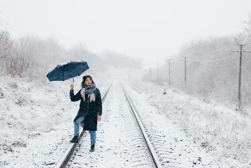 A cute young girl holds umbrella in the hands of the winter season. Winter portrait of young beautiful brunette woman. A cute young girl holds umbrella in the royalty free stock photo