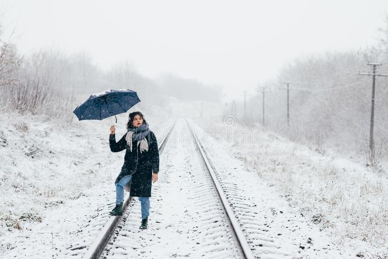 A cute young girl holds umbrella in the hands of the winter season. Winter portrait of young beautiful brunette woman. A cute young girl holds umbrella in the stock photo