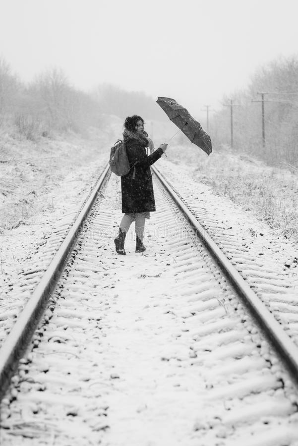 A cute young girl holds umbrella in the hands of the winter season. Winter portrait of young beautiful brunette woman. A cute young girl holds umbrella in the royalty free stock image